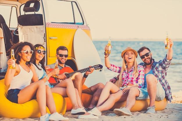 Samen genieten van de zomertijd. groep gelukkige jonge mensen die samen plezier hebben terwijl ze op het strand zitten in de buurt van hun retro busje