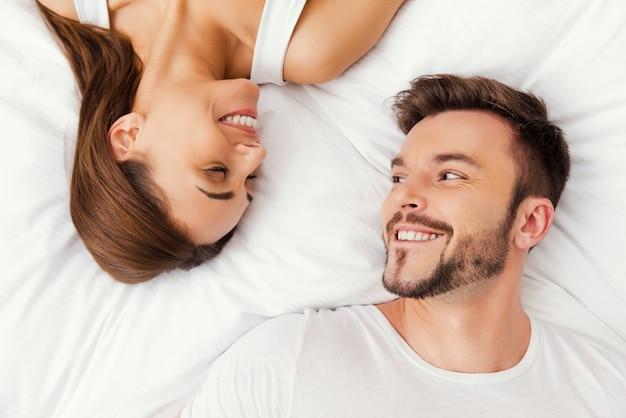 Samen genieten van elk moment. bovenaanzicht van een mooi jong liefdevol paar dat samen in bed ligt en naar elkaar kijkt