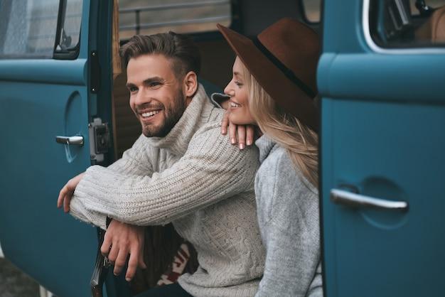 Samen genieten van elke minuut. mooie jonge vrouw haar vriendje kijken en glimlachen zittend in blauwe retro-stijl minibusje