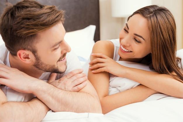 Samen genieten van tijd. mooie jonge verliefde paar samen in bed liggen en kijken naar elkaar met een glimlach