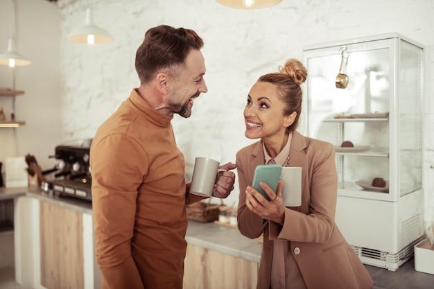 Samen grappen maken. glimlachende mooie vrouw die grappige foto op haar smartphone toont aan haar knappe collega.