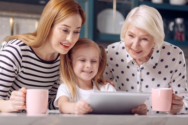 Samen grappiger. klein meisje toont een video op de tablet aan haar moeder en grootmoeder terwijl de vrouwen koffie drinken uit roze kopjes Premium Foto