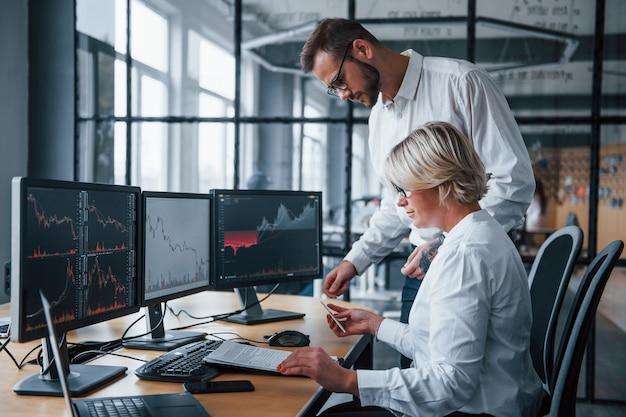 Samen informatie analyseren. twee effectenmakelaars in formele kleding werken op kantoor met financiële markt.