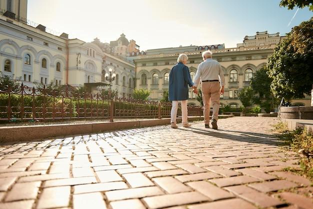 Samen is onze favoriete plek om achteraanzicht te zijn van een ouder echtpaar dat handen vasthoudt tijdens het wandelen