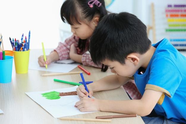 Samen maken aziatische voorschoolse studenten huiswerk door op een kleur te tekenen