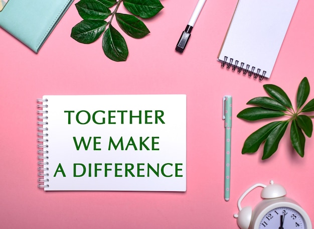 Samen maken we een verschil is geschreven in het groen op een wit notitieblok op een roze oppervlak omgeven door notitieblokken, pennen, witte wekker en groene bladeren