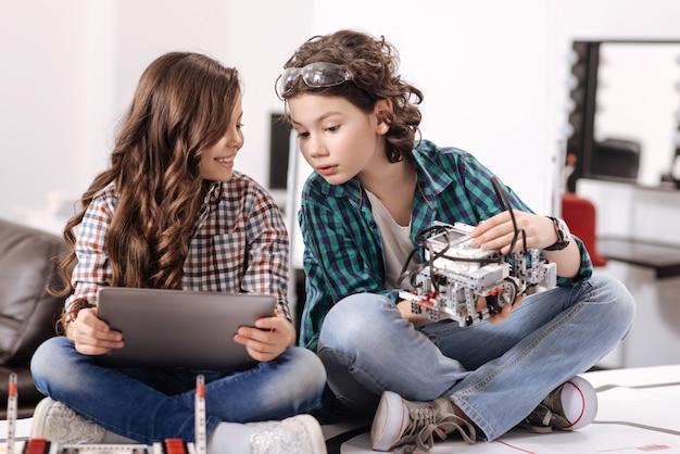 Samen nieuwe technologieën verkennen. grappige betrokken vriendelijke kinderen die thuis zitten en gadgets en apparaten gebruiken terwijl ze plezier hebben Premium Foto