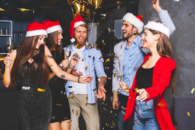 Samen nieuwjaar vieren. groep mooie jonge mensen in santa hoeden kleurrijke confetti gooien en op zoek gelukkig