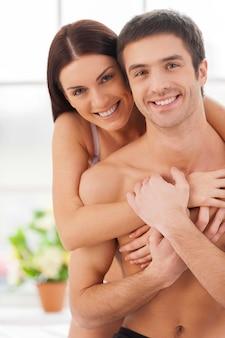 Samen ochtendtijd doorbrengen. vrolijk jong liefdevol stel dat samen in bed zit en vasthoudt