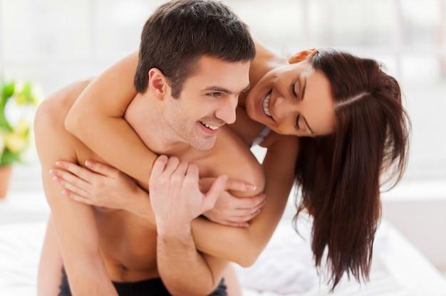 Samen ochtendtijd doorbrengen. vrolijk jong verliefd stel dat plezier heeft terwijl ze samen in bed zitten