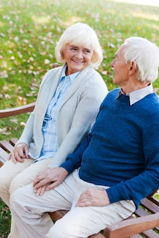 Samen ontspannen in het park. bovenaanzicht van een gelukkig senior koppel dat handen vasthoudt en elkaar aankijkt terwijl ze samen op de bank in het park zitten