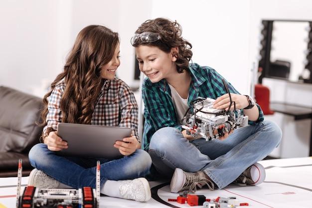 Samen op internet surfen. grappige vrolijke dynamische kinderen die thuis zitten en gadgets en apparaten gebruiken terwijl ze belangstelling tonen