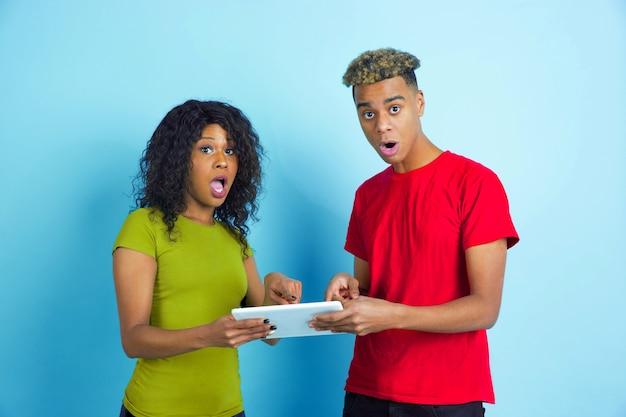 Samen op tablet wijzen. jonge emotionele afro-amerikaanse man en vrouw in kleurrijke vrijetijdskleding op blauwe achtergrond. mooi koppel. concept van menselijke emoties, gezichtsuitdrukkingen, relaties, advertentie.
