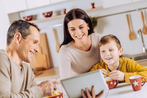 Samen plezier maken. aangename jongeman die de tablet aan zijn gezin laat zien en samen naar de video kijkt terwijl ze 's ochtends aan het ontbijten zijn