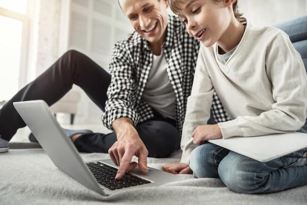 Samen plezier maken. knappe opgetogen donkerharige man glimlachend en typen op de laptop en zijn zoon zit naast hem op de vloer