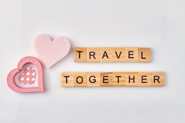 Samen reizen gemaakt met houten alfabetblokjes. romantisch reisconcept op witte achtergrond.