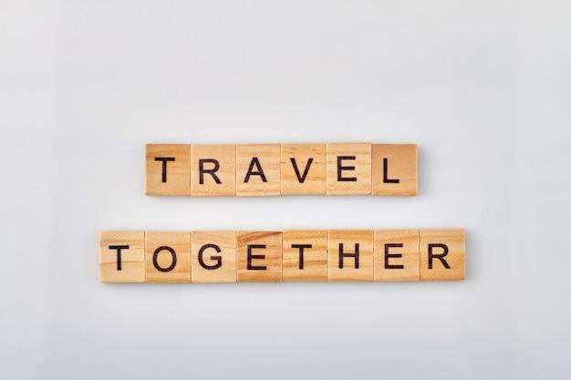 Samen reizen is altijd leuk en plezierig. houten blokken gemaakt woorden op witte achtergrond.