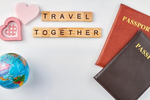 Samen reizen is heel romantisch. paspoorten en roze harten met bol op witte achtergrond.