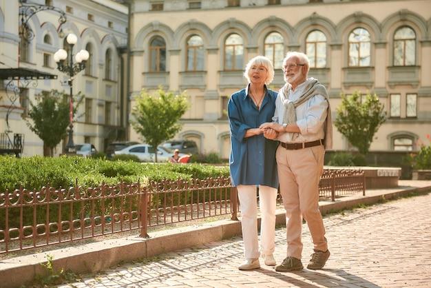 Samen reizend gelukkig en mooi bejaarde echtpaar hand in hand terwijl ze samen wandelen