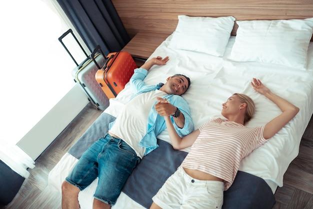 Samen rusten. verliefde paar liggen samen in een hotelbed in hun kleren en met uitgepakte reiskoffers.