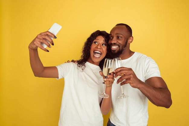 Samen selfie maken. gelukkig afrikaans-amerikaans paar geïsoleerd op gele muur. concept van menselijke emoties, gezichtsuitdrukking, liefde, relaties, romantische vakanties.