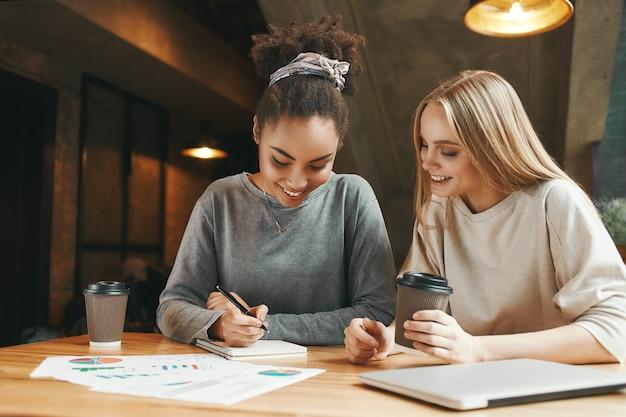 Samen slagen zakenvrouwen hebben een vergadering in een modern café