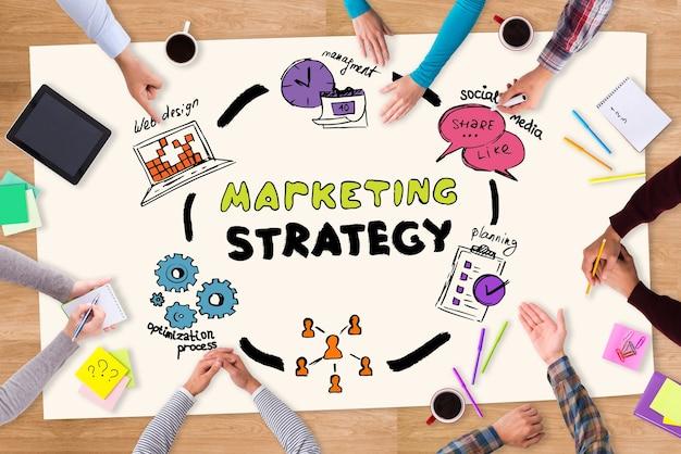 Samen strategie plannen. bovenaanzicht van papier met kleurrijke schetsen op de houten tafel en mensen die eromheen zitten