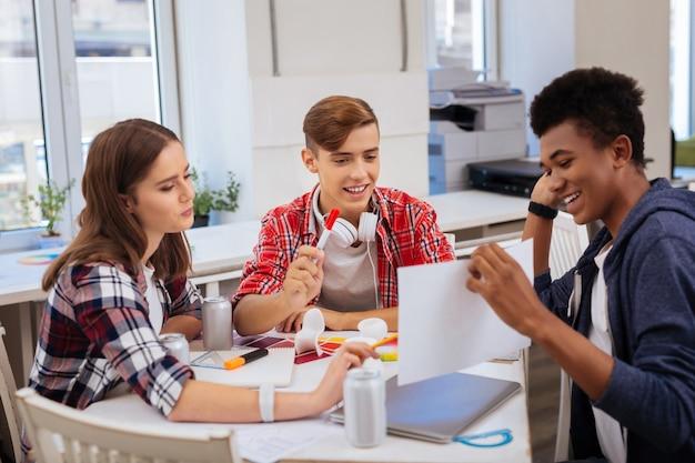 Samen studeren. drie slimme opgewonden postdoctorale studenten die enorm genieten van het proces van samen studeren