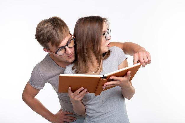 Samen studeren en mensenconcept - een paar jonge grappige mensen die een boek lezen