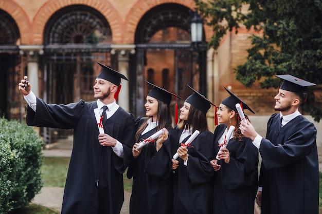Samen studeren. groep studenten staan op de campus en maken selfie