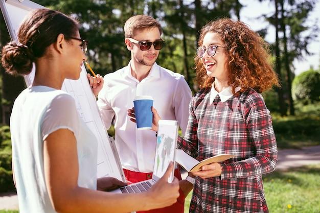 Samen studeren. uitbundig krullend meisje dat koffie houdt en met haar vrienden over het project praat