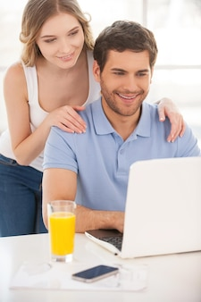 Samen surfen op het net. knappe jongeman die aan tafel zit en laptop gebruikt terwijl zijn vriendin achter hem staat