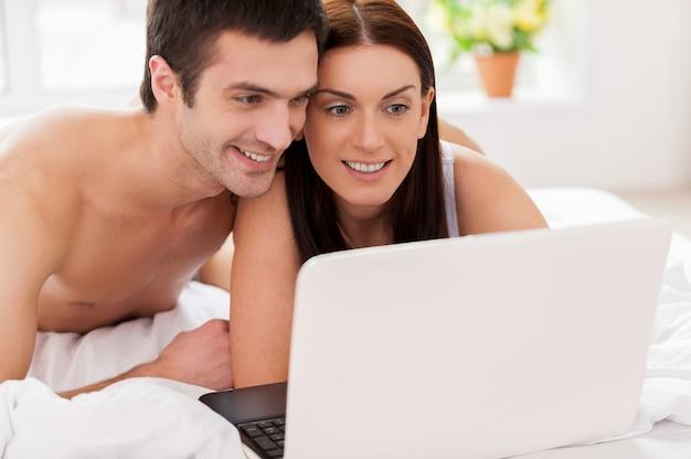 Samen surfen op het web. vrolijk jong liefdevol stel dat in bed ligt en samen computer gebruikt