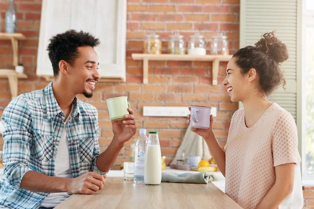 Samen thuis tijd doorbrengen. vrolijke bebaarde man en zijn vrouw drinken 's ochtends thee of melk, hebben een goed humeur,