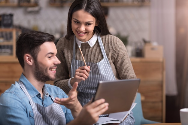 Samen tijd doorbrengen. blij dat ontspannen paar lacht en aantekeningen maakt tijdens het gebruik van de tablet.