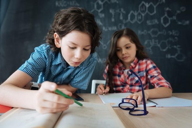 Samen vreemde talen studeren. geamuseerde nieuwsgierige bekwame kinderen die op school zitten en genieten van engelse les terwijl ze aantekeningen maken en nieuwe woorden leren