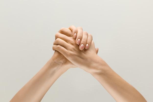 Samen winnen. lostup shot van mannelijke en vrouwelijke hand in hand geïsoleerd op grijze studio achtergrond. concept van menselijke relaties, vriendschap, partnerschap, familie. copyspace.