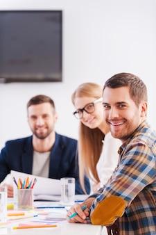 Samen zijn we sterker. drie vrolijke zakenmensen in slimme vrijetijdskleding die samen aan tafel zitten en naar de camera kijken