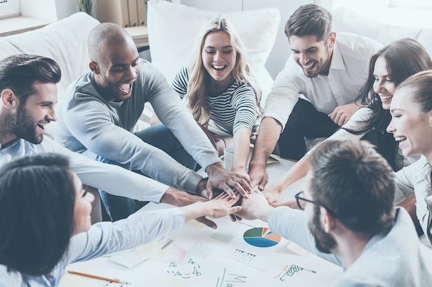 Samen zijn we sterker! groep gelukkige zakenmensen die elkaars hand vasthouden terwijl ze aan het bureau zitten