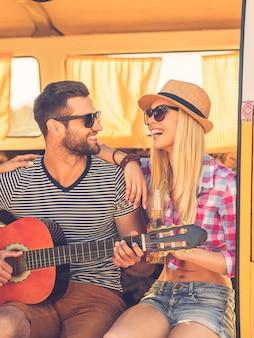 Samen zorgeloos tijd doorbrengen. knappe jongeman die in een minibusje zit en gitaar speelt terwijl zijn vriendin zich aan hem hecht en glimlacht