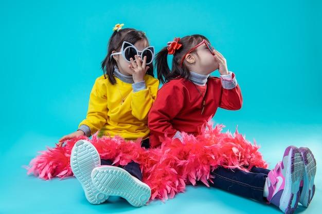 Samen zorgeloos zijn. twee gelukkige meisjes die op studiovloer zitten terwijl ze een bril dragen en benen bedekken met rode feestelijke boa