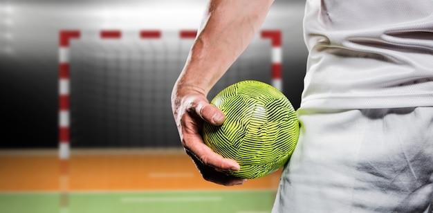 Samengesteld beeld van sportman die een bal houdt