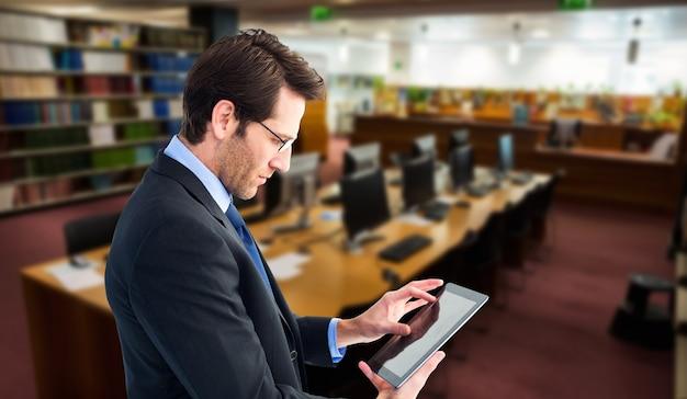 Samengesteld beeld van zakenman die staat tijdens het gebruik van een tablet-pc