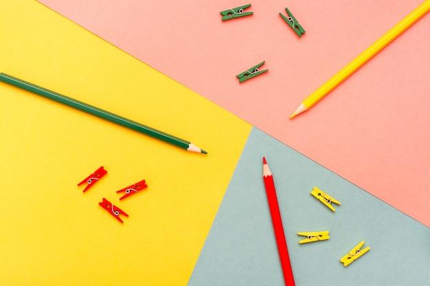 Samengevat zijn kleurpotloden en clips in de bovenaanzicht van geel, groen en rood