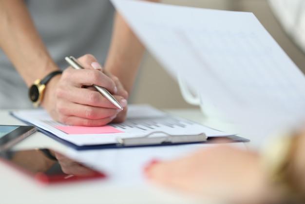 Samengevouwen handen met een pen naast zich is een rapport met commerciële grafieken. ontwikkelingsconcept voor kleine en middelgrote bedrijven