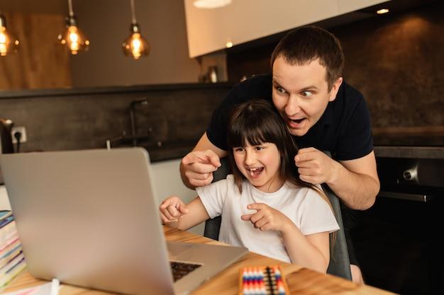 Samenhorigheid in het gezin en online leren. de vader en de dochter doen thuis online les met laptop