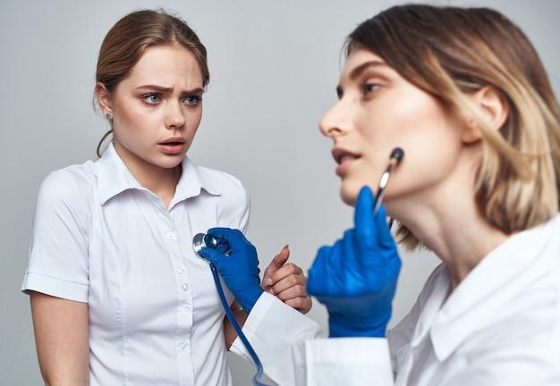 Samenstelling arts in een menigte en in blauwe handschoenen en een patiënt i