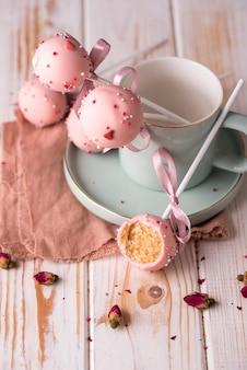 Samenstelling cake springt met prachtige lichte gebruiksvoorwerpen en in roze chocoladeroom met poeder op een houten achtergrond.