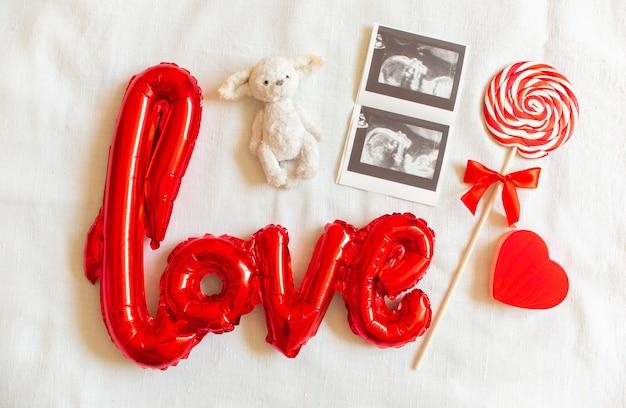 Samenstelling flat lag met baby accessoires op witte bed achtergrond. echografie, lolly, speelgoedbeer, hart.