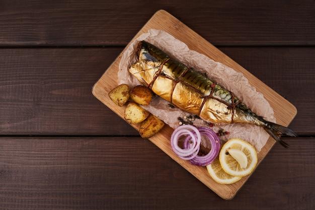 Samenstelling gerookte makreelvis met garnituur, aardappelen, citroengroenten, uien, geserveerd op een houten bordplaat bovenaanzicht